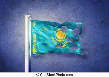 Torn flag of Kazakhstan flying against grunge background
