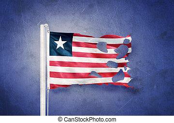 Torn flag of Liberia flying against grunge background