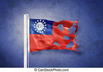 Torn flag of Myanmar flying against grunge background