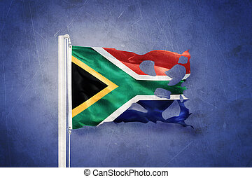 Torn flag of South Africa flying against grunge background.