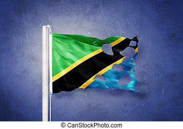 Torn flag of Tanzania flying against grunge background
