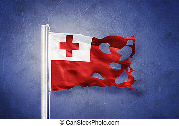 Torn flag of Tonga flying against grunge background