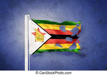 Torn flag of Zimbabwe flying against grunge background