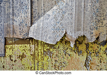 Torn vintage wallpaper shreds and peeling paint wall texture.