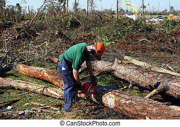A man using a chainsaw to cleanup after a tornado