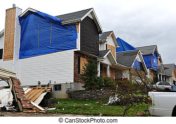Homes damaged a tornado and covered in tarps