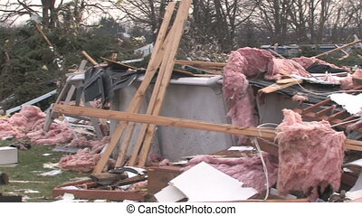Panning across house wreckage in the path of destruction from a tornado, and stopping on a large burning fire