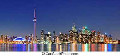 Toronto cityscape panorama at dusk over lake with colorful ...