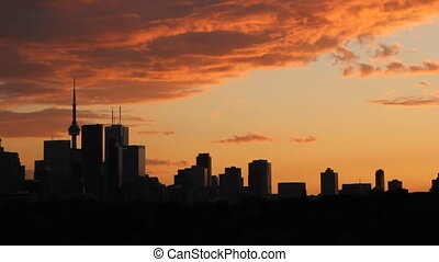 View of downtown Toronto from the west. Orange sunset timelapase.