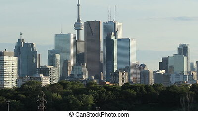 View of downtown Toronto from the west. Green trees of Don Valley in the foreground.