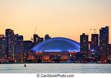 Toronto sunset silhouette at dusk over lake with urban...