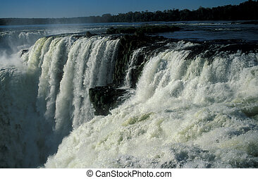 Iguacu Falls - Torrent of water flowing over the lip of...