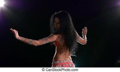 Torso of a beautiful belly dancer on a black, back light, slow motion