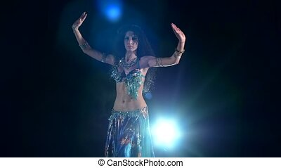 Torso of a beautiful belly dancer on a black smoke, back...