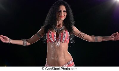 Torso of a beautiful young girl belly dancer on a black, back light, cam moves down, slow motion