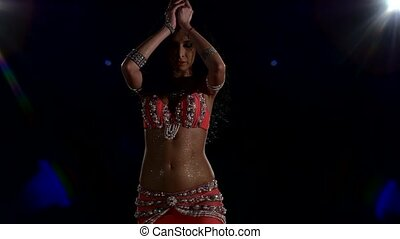Torso of a beautiful young girl belly dancer on a black, back light, cam moves up