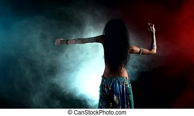 Torso of a beautiful, young girl female belly dancer on a black, smoke background, back light, cam moves down
