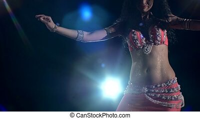 Torso of a beautiful young girl belly dancer on a black, back light, cam moves down