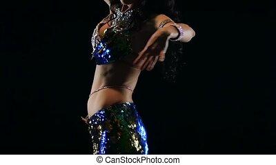 Torso of a exotic female belly dancer. Black background....