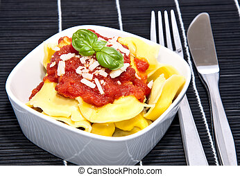 Tortellini in a bowl on black background