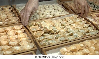 Tortellini lying in wooden trays in a restaurant kitchen -...