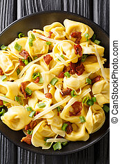 Tortelloni with bacon, cheese and green onions close-up in a plate. Vertical top view