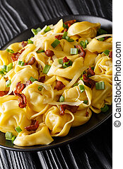 Tortelloni with bacon, cheese and green onions close-up in a plate. vertical