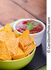 Tortilla chips with spicy tomato salsa with jalapeno