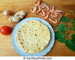 Tortilla on plate with shrimps, nettles, tomato, onion and...