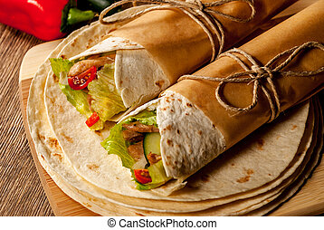 Mexican tortilla wrap with meat and vegetables on wood table