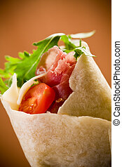Delicious tortillas stuffed with bacon and colorful arugula salad