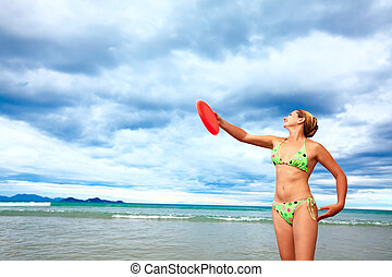 Tossing a frisbee - Young woman is tossing a frisbee on the...