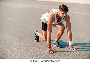 total, concentration., confiado, joven, muscular, hombre estar de pie, en, línea de salida, y, pareciendo delantero