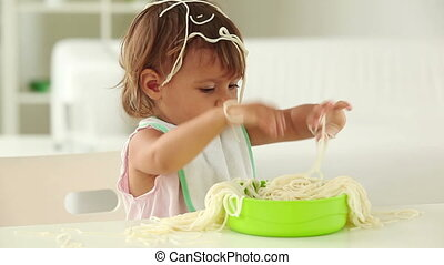 Little girl making a total mess of spaghetti