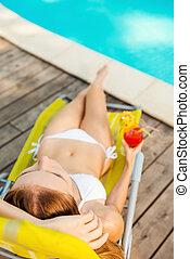 total, relaxamento, por, a, pool., vista superior, de, bonito, mulher jovem, em, biquíni branco, segurando, coquetel, em, dela, mão, enquanto, relaxante, em, cadeira convés, perto, a, piscina