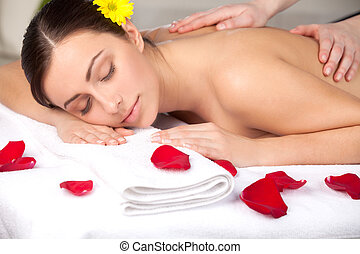 Total relaxation. Attractive young woman with flower in head lying on front while massage therapist massaging her back