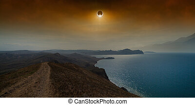 Total solar eclipse in dark red sky above sea and mountains