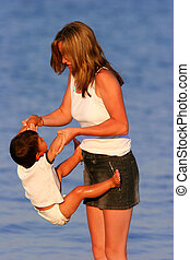 Tanned mother on a beach with her young baby boy in a nappy, swinging him up by the arms.