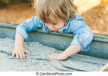 Tottler boy playing in the sandbox