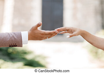 touch of hands. Young married couple holding hands, ceremony wedding day. hand of the groom and the bride, guys and girls, outdoors