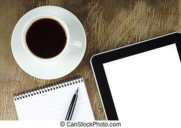 Touch screen device, cup of coffee, notepad and pen on an old wooden background close-up