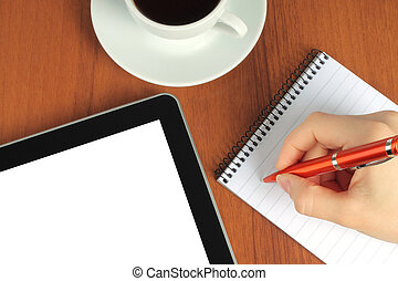 Touch screen device, notepad, writing hand and cup of coffee on wooden background close-up