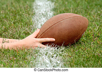 Touchdown - Hands with football reaching over white line