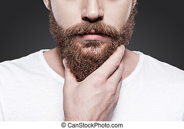 Touching his perfect beard. Close-up of young bearded man...
