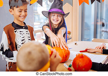 Brother and sister wearing nice funny Halloween costumes touching pumpkins