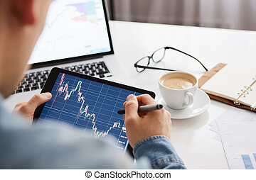 Touching stock market graph on a touch screen device. Trading on stock market concept