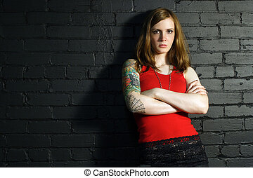 Tough - A young female with full arm tattoo leaning up...