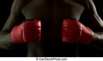 Tough boxer punching fists together with red gloves in slow...