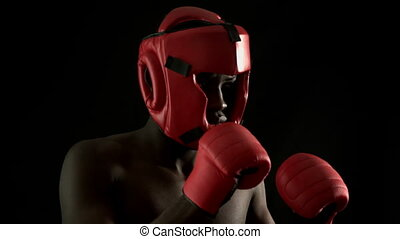 Tough boxer punching with red gloves in slow motionTough...