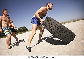 Tough male athlete flipping a truck tire. Young people doing crossfit exercise on beach.